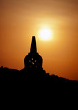 Decorative Buddhist stupa. Silhouette at sunset. Stock Photos