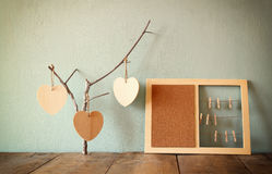 Decorative bulletin board with ropes and wooden clothespins and hanging hearts over wooden table. ready for text or mockup. retro Royalty Free Stock Photo