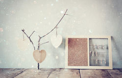 Decorative bulletin board with ropes and wooden clothespins and hanging hearts over wooden table. ready for text or mockup. retro Stock Image