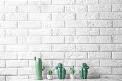 Decorative cacti on table near brick wall, space for text. Interior decor royalty free stock photography