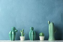 Decorative cacti on table near color wall, space for text. Interior decor stock photography