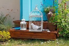 Decorative cage with ceramic bird, candlestick and flowers in pots stand on the steps Royalty Free Stock Photo