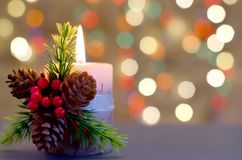 Decorative candle with berries and cones stock photos