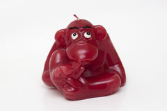 Decorative candle in the shape of a monkey. Aromatic candle in the shape of a monkey, fingers in mouth Stock Photos
