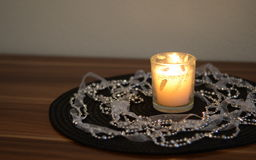 Decorative candle on the table. Decorative candle placed on a napkin on the table and rotated beads Royalty Free Stock Photo
