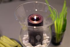 Decorative candle in a transparent glass vase. With small pebbles on the bottom Stock Images