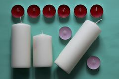 Decorative candles arranged in a row. On a mint background stock photography