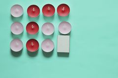 Decorative candles arranged in a row. Decorative candles and matchboxes arranged in a row. On a mint background stock image