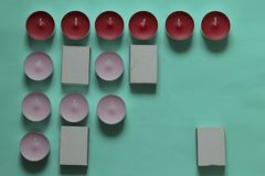 Decorative candles arranged in a row. Decorative candles and matchboxes arranged in a row. On a mint background royalty free stock photos