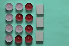 Decorative candles arranged in a row. Decorative candles and matchboxes arranged in a row. On a mint background royalty free stock photography