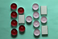 Decorative candles arranged in a row. Decorative candles and matchboxes arranged in a row. On a mint background stock photography