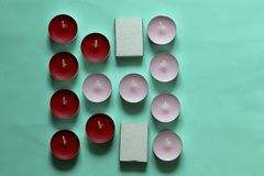 Decorative candles arranged in a row. Decorative candles and matchboxes arranged in a row. On a mint background royalty free stock image
