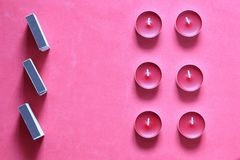 Decorative candles and matchboxes arranged in a row. On a pink background.  stock image