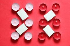 Decorative candles and matchboxes arranged in a row. On a pink background.  royalty free stock image