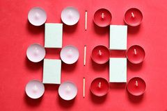 Decorative candles and matchboxes arranged in a row. On a pink background.  royalty free stock photo