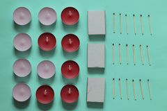 Decorative candles arranged in a row. Decorative candles, matchboxes and matches are arranged in a row. On a mint background royalty free stock images