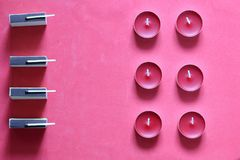 Decorative candles, matchboxes and matches are arranged in a row. On a pink background.  stock images