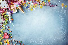 Decorative carnival party background. With colorful hats, streamers, unicorn costumes, candy, confetti and hearts as a border against a textured blue background