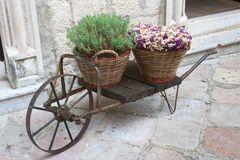 Decorative cart with baskets and flowers on the street Royalty Free Stock Photo