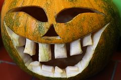 Decorative carved gouged out Halloween pumpkin as Jack-o`-lantern, smiling with large teeth. And half closed eyes royalty free stock photos