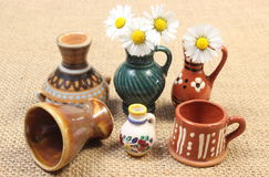 Decorative ceramic vases and white daisies on jute canvas Royalty Free Stock Photo