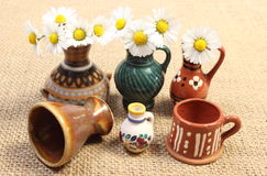 Decorative ceramic vases and white daisies on jute canvas Stock Photo