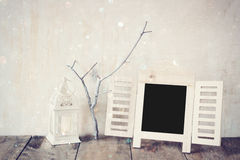 Decorative chalkboard frame and little tree branches over wooden table. ready for text or mockup. retro filtered image Royalty Free Stock Photo