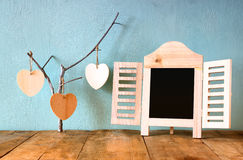 Decorative chalkboard frame and wooden hanging hearts over wooden table. ready for text or mockup. retro filtered image Royalty Free Stock Photo