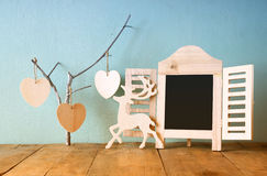 Decorative chalkboard frame and wooden hanging hearts over wooden table. ready for text or mockup. retro filtered image Stock Photos