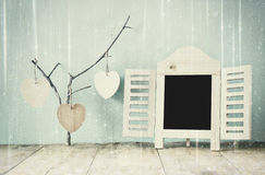 Decorative chalkboard frame and wooden hanging hearts over wooden table. ready for text or mockup. retro filtered image with
