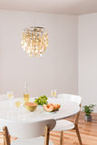 Decorative chandelier and elegant table with white wine Royalty Free Stock Photos