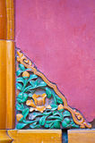 Decorative Chinese Corner Piece. Traditional Chinese corner detail featuring flowers and leaves against a red wall Royalty Free Stock Photo
