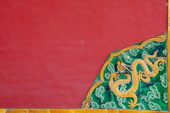 Decorative Chinese Corner Piece. Traditional Chinese corner detail featuring a dragon against a red wall Royalty Free Stock Image