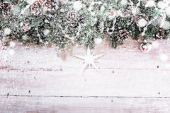Decorative Christmas background with snow. Falling on a still-life of pine cones and foliage decorated with beads and a star ornament on rustic wooden boards stock photos