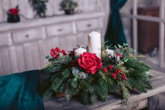 Decorative Christmas basket with candles and roses. On a wooden table Stock Photos