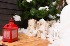 Decorative Christmas candles and lantern. Decorative Christmas candles and colorful red lantern on a wooden table in front of a Christmas tree with snow Royalty Free Stock Photos