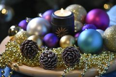 Decorative Christmas composition with lights, balls,. Decorative Christmas composition with candle, balls, cones. Coloured dreams for Christmas Time Stock Images