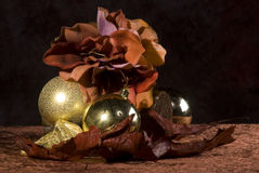 Decorative Christmas display. A decorative still life composition with flowers and golden Christmas ornaments stock images