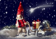Decorative Christmas doll pulling a sled and gifts. Decorative Christmas doll pulling a sled with gifts through winter snow under a starry sky with a shooting Stock Image