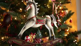 Decorative christmas horse moving in front of the christmas tree stock footage