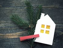 Decorative Christmas house from white paper and a fir-tree branch on a textural wooden board. Stock Image
