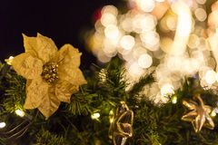 Decorative christmas ornaments baubles and flowers on evergreen branches of a coniferous tree at the outdoor christmas markets Stock Photography