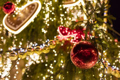 Decorative christmas ornaments baubles on green evergreen branches of a coniferous tree Stock Images