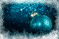 Decorative Christmas tree ball in front of sparkling background. With ice crystals frame Royalty Free Stock Image