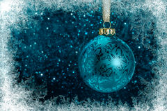 Decorative Christmas tree ball in front of sparkling background. With ice crystals frame Royalty Free Stock Photography