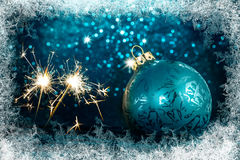 Decorative Christmas tree ball in front of sparkling background. Decorative Christmas tree ball with sparklers in front of sparkling background with ice crystals Royalty Free Stock Photo