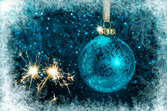 Decorative Christmas tree ball in front of sparkling background. Decorative Christmas tree ball with sparklers in front of sparkling background with ice crystals Royalty Free Stock Photography