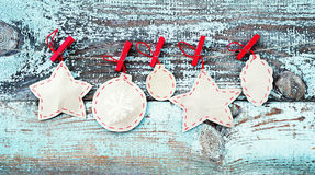 Decorative Christmas tree decorations from paper on a rope against the background of the old removed board Stock Image