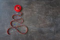 Decorative christmas tree made from red curly ribbon and red bow. Star on a dark brown textural background. Coil with red ribbon in the form of a xmas tree. DIY stock photo