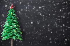 Decorative Christmas tree from paper isolated on dark background with snow flakes, holiday background stock photos